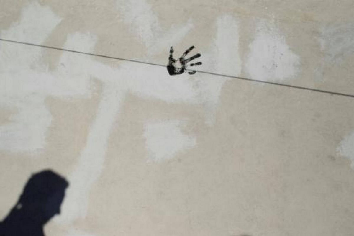The shadow of a reveller is cast on a wall as a handprint is seen during the annual Cascamorras festival in Baza, Spain on Sept 6, 2017.