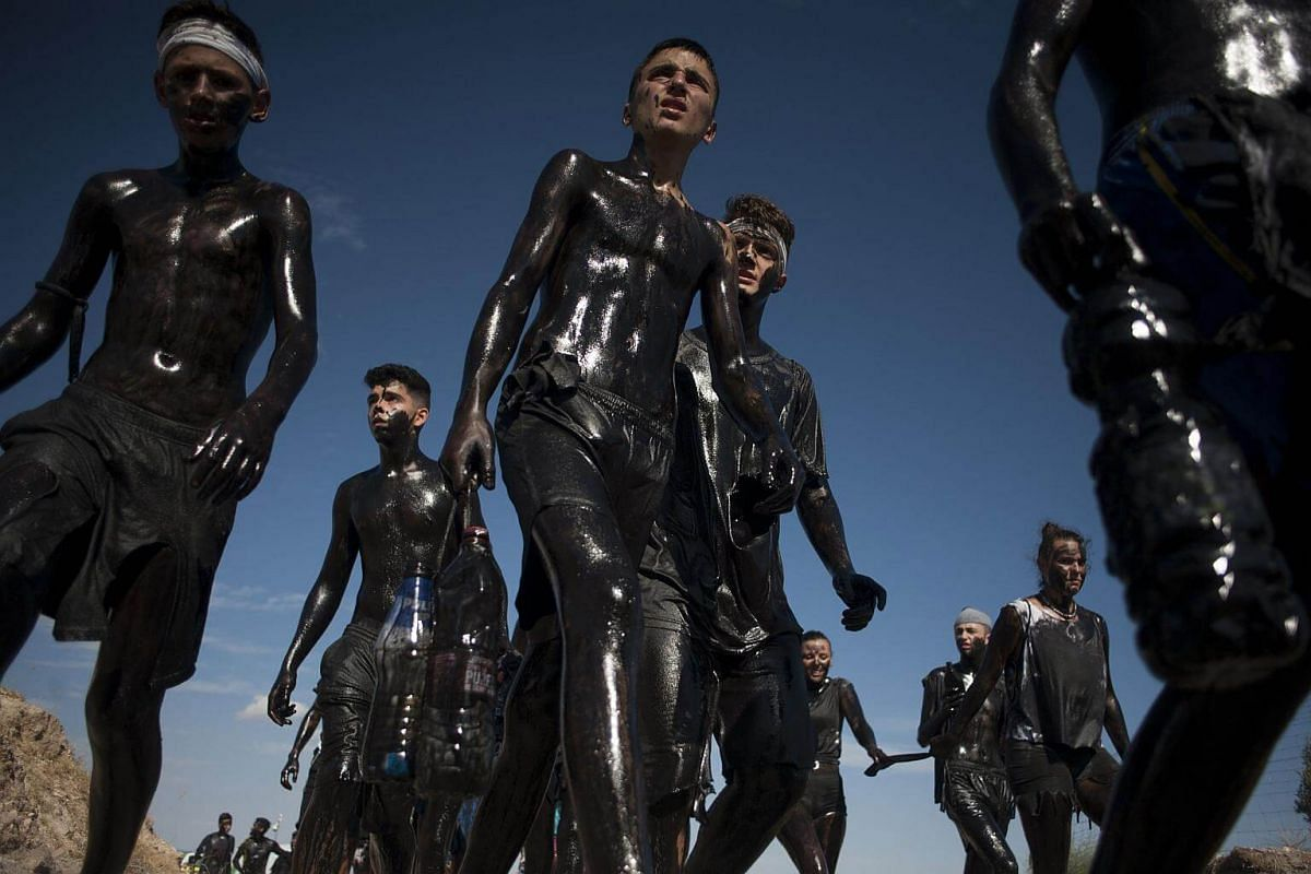 People covered in black grease during the traditional festivities of the Cascamorras, in Baza, on Sept 6, 2017.