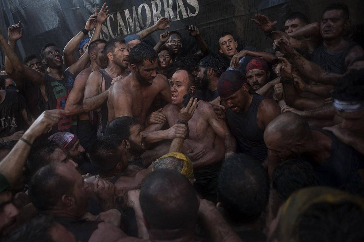 People covered in black grease take part in the three-day festival of the Cascamorras, in Baza, on Sept 6, 2017.