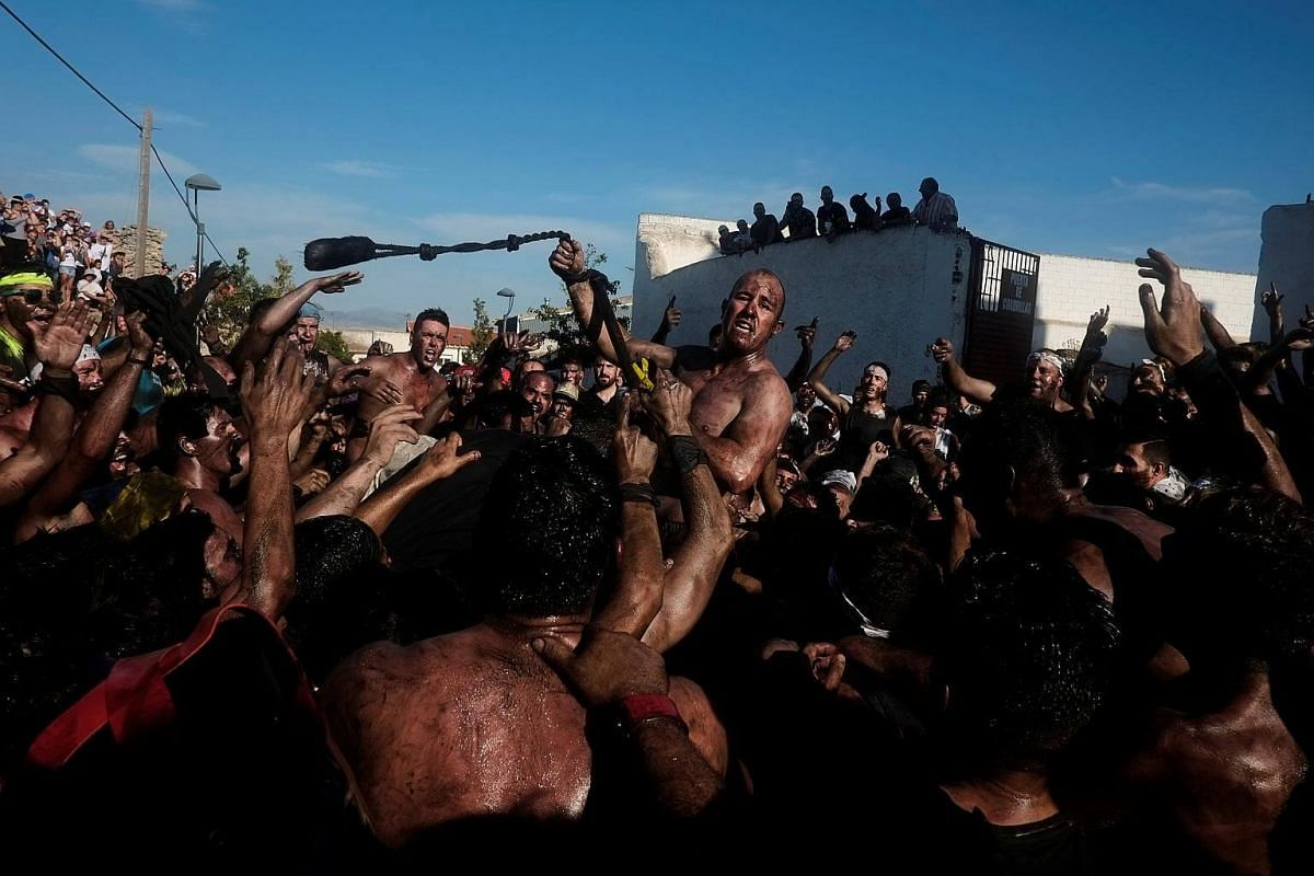 Revellers covered in grease having a slippery time in the annual Cascamorras festival in Baza, Spain on Sept 6, 2017.
