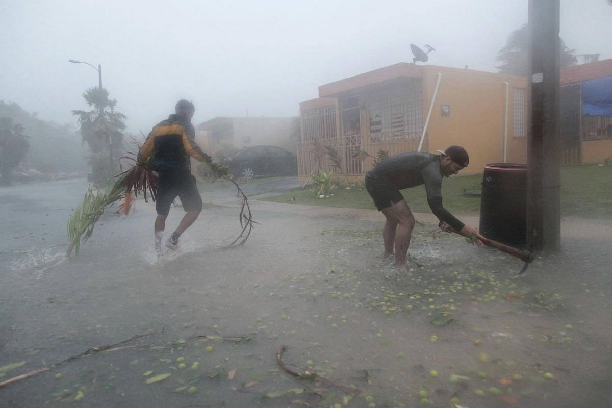 People pick up debris as Hurricane Irma howled past Puerto Rico after thrashing several smaller Caribbean islands, in Fajardo, on Sept 6, 2017.