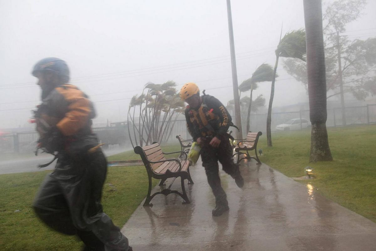 Members of the civil defense force run as Hurricane Irma howls past Puerto Rico after thrashing several smaller Caribbean islands, in Fajardo, on Sept 6, 2017.