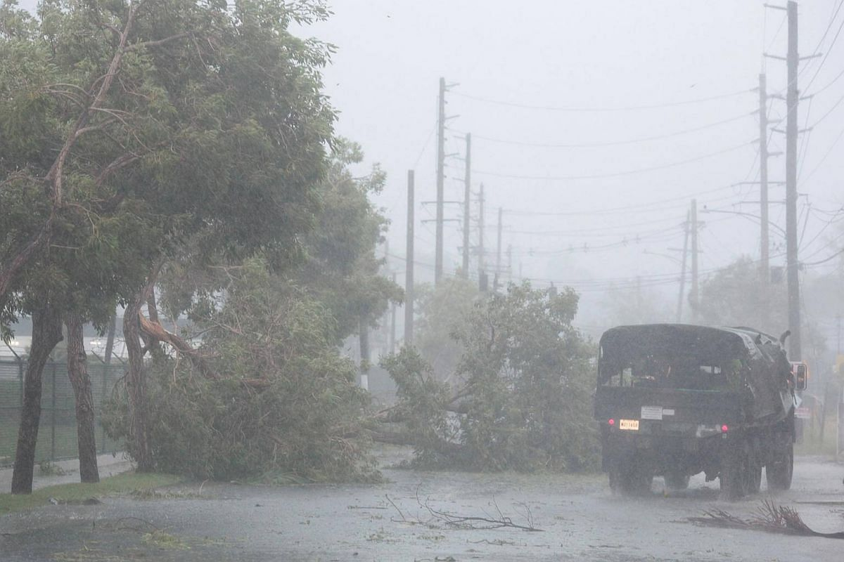 A truck drives past fallen trees as Hurricane Irma howls past Puerto Rico after thrashing several smaller Caribbean islands, in Fajardo, on Sept 6, 2017.