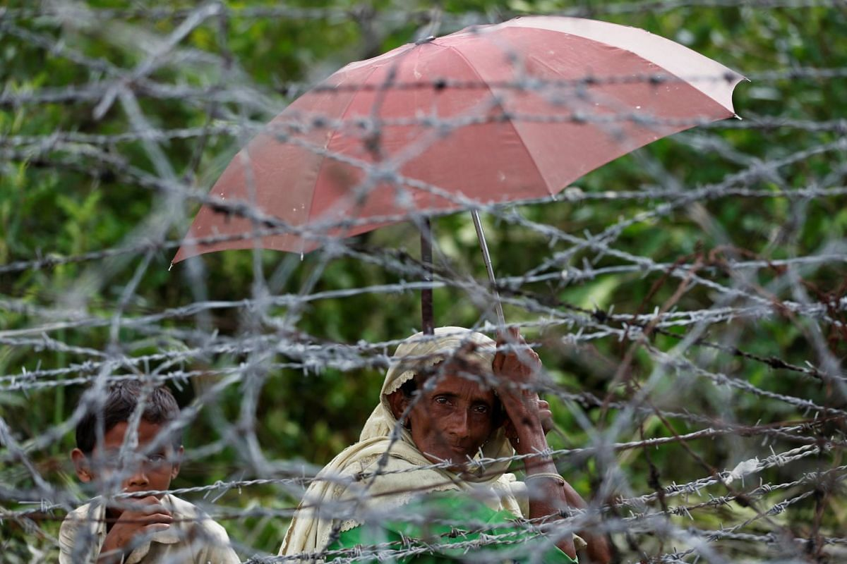 A Rohingya refugee woman and boy looks on through barbed wire as they wait for boat to cross the border through Naf river in Maungdaw, Myanmar, on Sept 7, 2017.PHOTO: REUTERS
