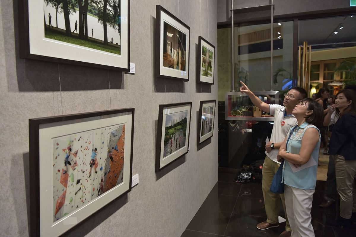 Guests looking at framed photographs taken by Straits Times photojournalists Neo Xiaobin and Kua Chee Siong at the Leica Galerie at the Fullerton Hotel on Sept 7, 2017. Scenes of Singapore - A collaboration between The Straits Times and Leica camera