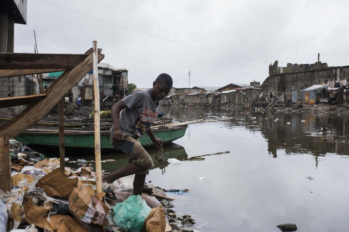 A man walks along a flooded area with debris carried by strong winds in Cap Haitian, Haiti on Sept 7, 2017.