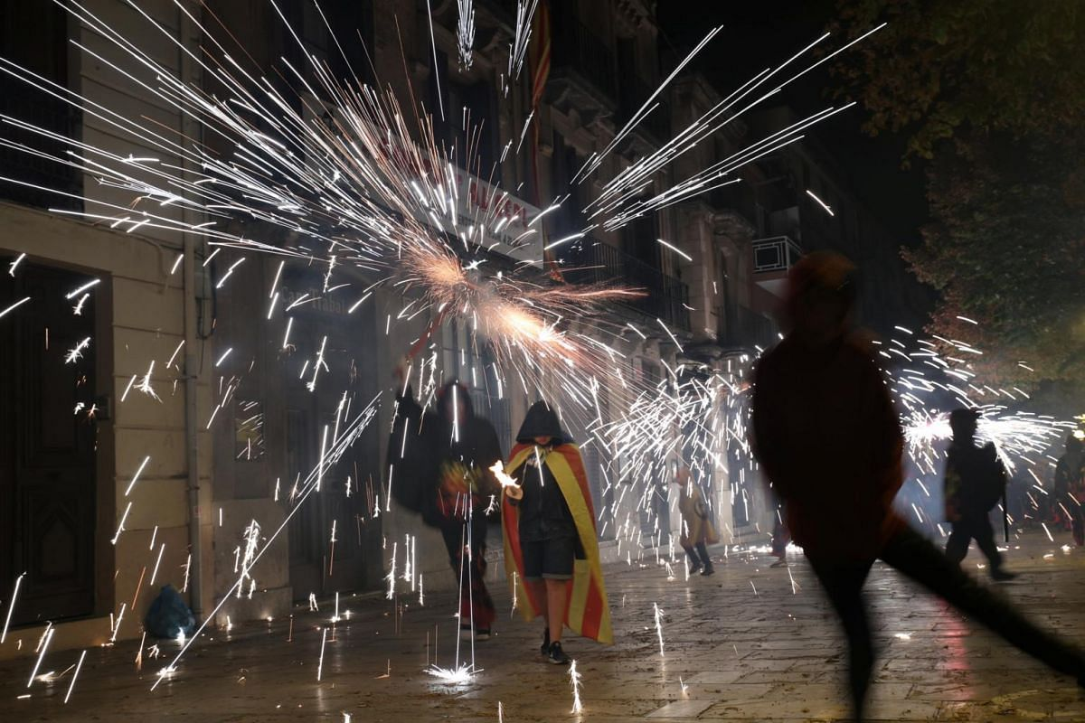 A boy wearing an Estelada (Catalan separatist flag) marches with a torch, under sparks set off by a demonstrator dressed as a devil, during a pro-independence demonstration in Vilafranca del Penedes, Spain, on Sept 10, 2017.