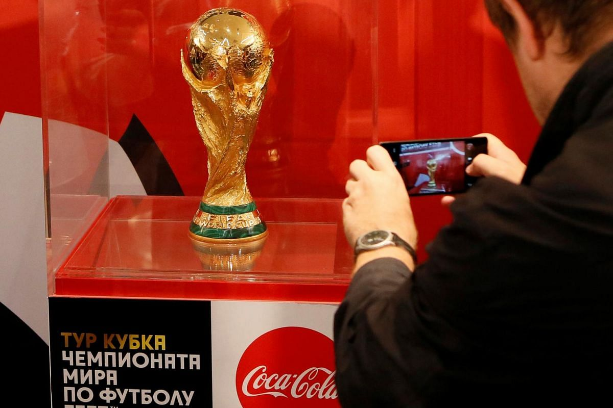 A man takes a picture of the World Cup trophy after a news conference devoted to the Fifa World Cup Trophy Tour in Krasnoyarsk, Siberia, Russia, on Sept 10, 2017.
