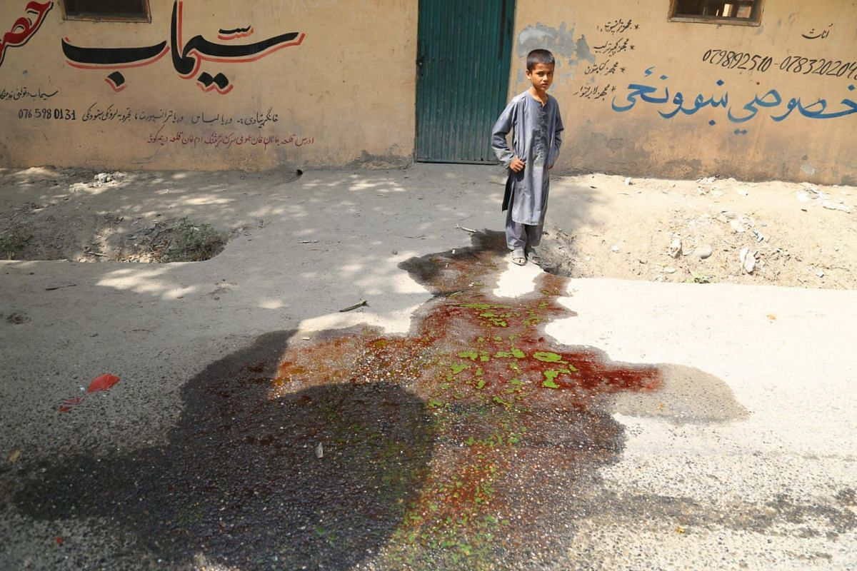 A boy stands beside blood stains at the scene of a bomb blast in Jalalabad, Afghanistan, on Sept 10, 2017.