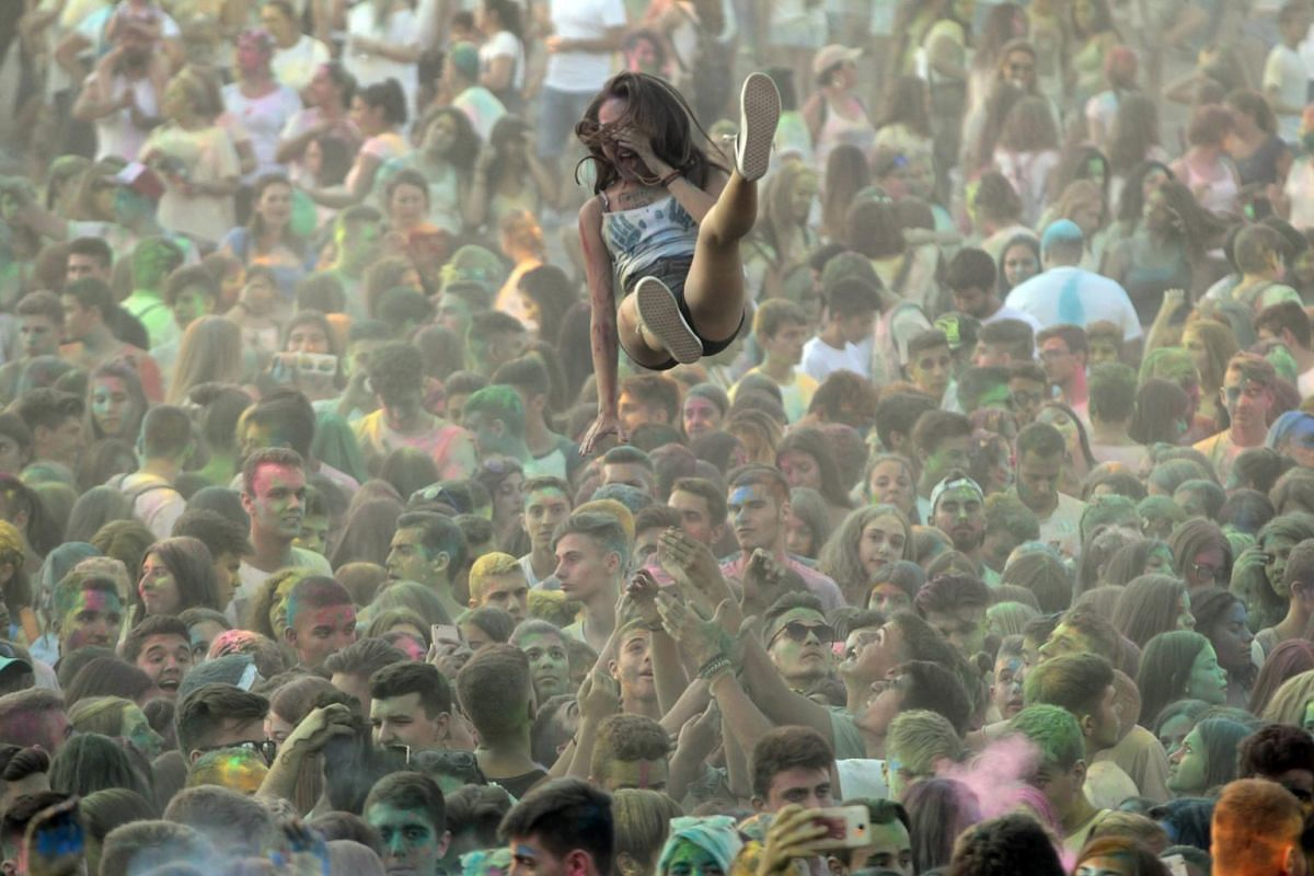 """A reveller is tossed in the air during the 6th annual """"Day of Colours"""" in Thermi, near the northern port city of Thessaloniki, Greece, on Sept 10, 2017."""