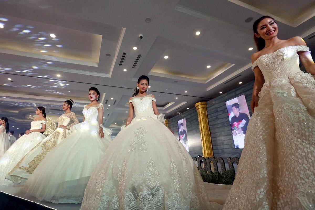 Models present wedding dresses creation of local designer Aung Myat Thu during the Aroma wedding fair 2018 in Yangon, Myanmar, on Sept 10, 2017.