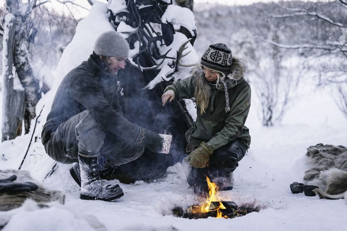 Tinja Myllykangas and Alex Schwarz make a fire outside their cabin and enjoy a hot beverage and hot meal after a husky ride.