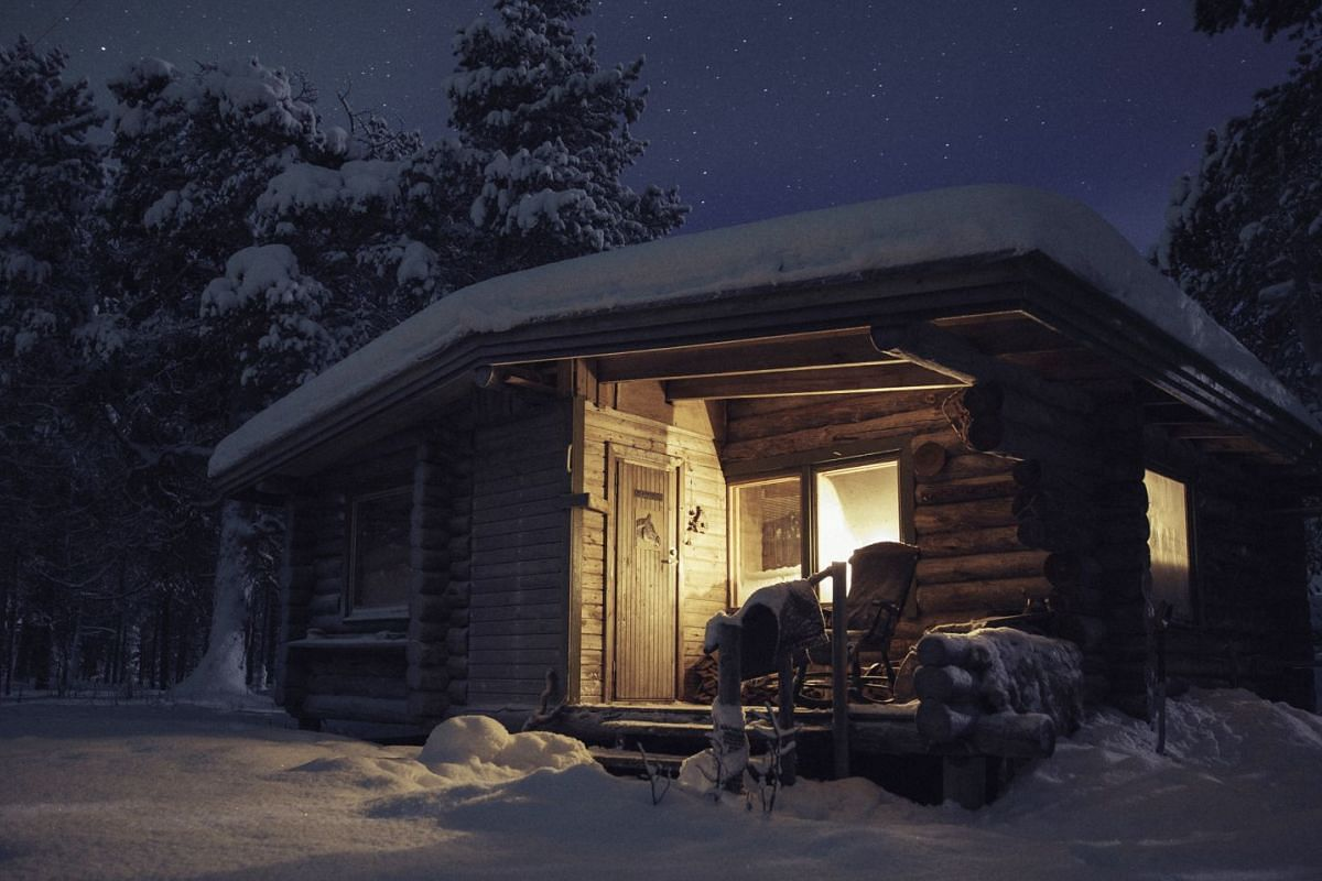 The writer's cabin is lit by candles and contains a wood stove for cooking and warmth, and a cosy corner for a sleeping bag.