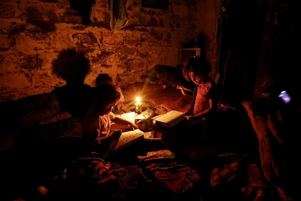 Palestinian children do their homework during a power cut in an impoverished area in Gaza City, on Sept 11, 2017.