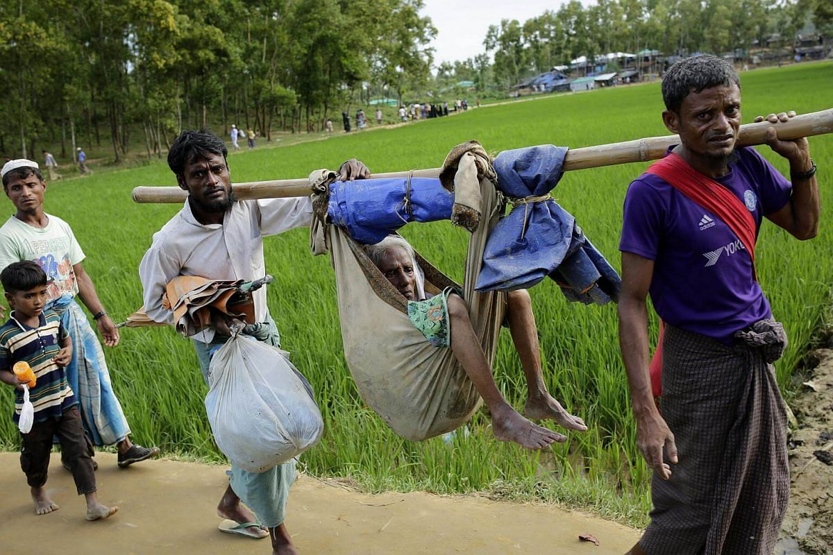 Two Rohingya men carry their mother in a hammock as they walk into a refugee camp in Ukhiya, Cox's Bazar, Bangladesh, on Sept 11, 2017.
