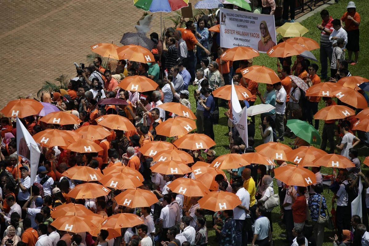 Supporters carrying orange umbrellas with the initial H as president-elect Madam Halimah Yacob gives her speech at the nomination centre on Sept 13, 2017.