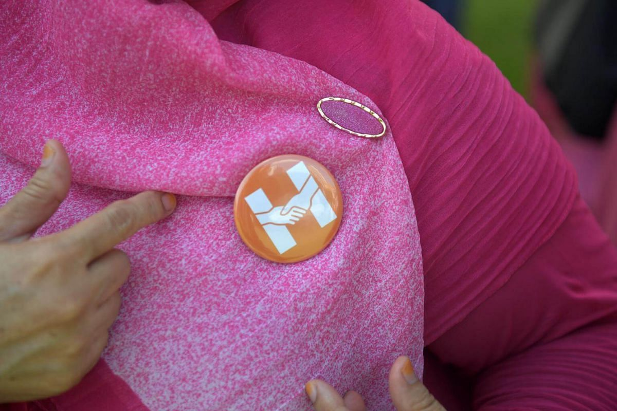 A supporter with a badge at the People's Association HQ in King George's Avenue.
