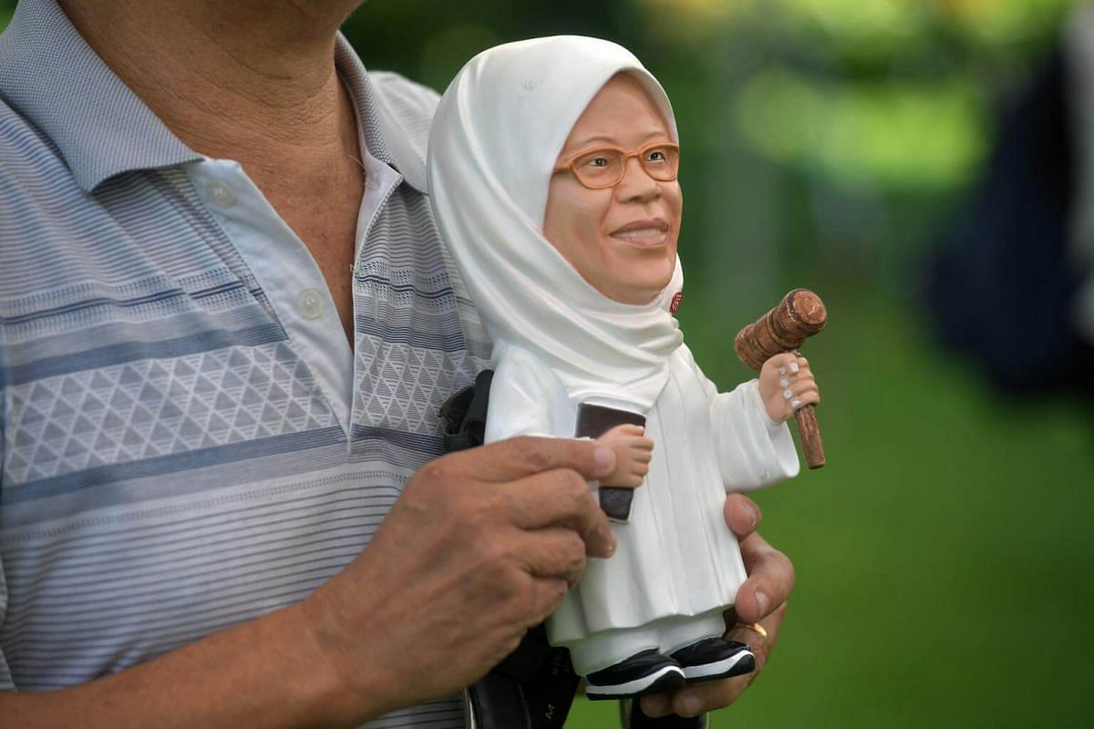 A man holds a figurine of Madam Halimah Yacob at the People's Association HQ in King George's Avenue.