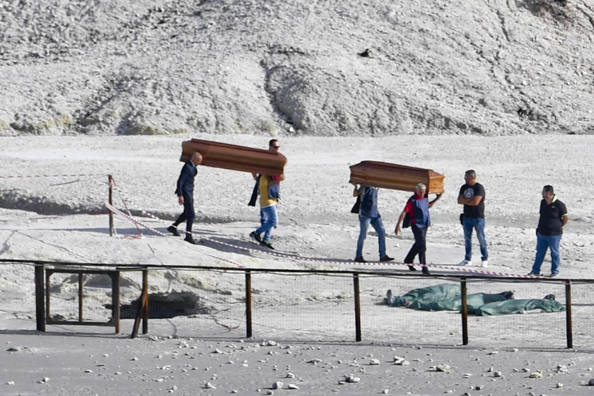 The coffins of three dead people are carried away out of the volcanic zone, where three people died in the crater at Pozzuoli, Naples, Italy, on Sept 12, 2017.