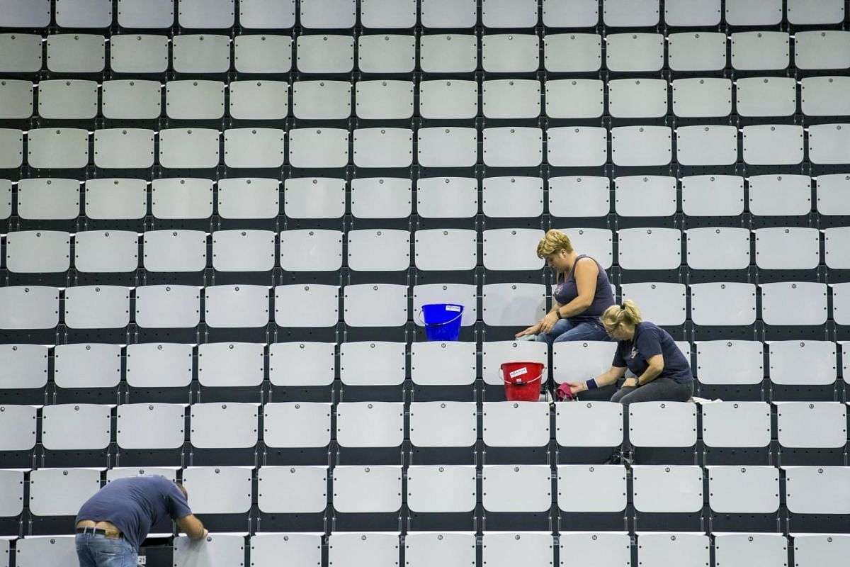 Workers clean seats at the Swiss Tennis Arena in Biel, Switzerland, on Sept 12, 2017.