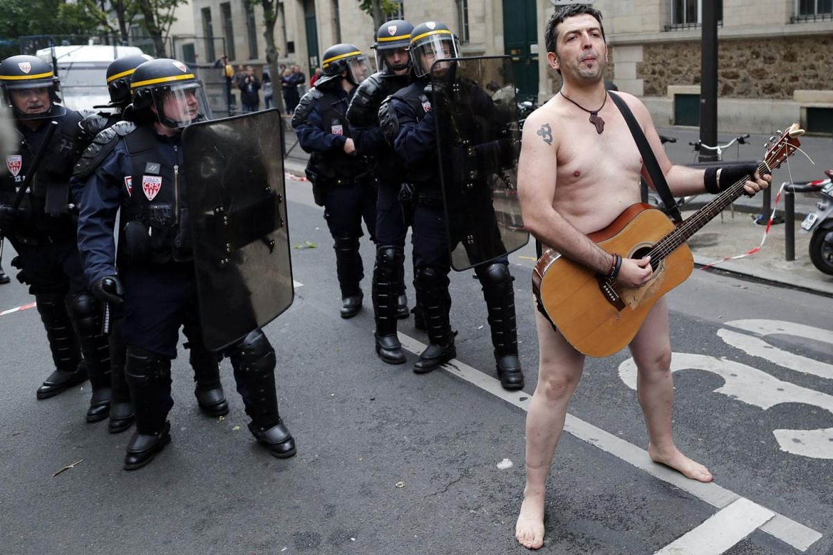 A naked protester plays guitar in front of French riot police officers as thousands of protesters have gathered during a demonstration against French government's labor reforms in Paris, France, on Sept 12, 2017.