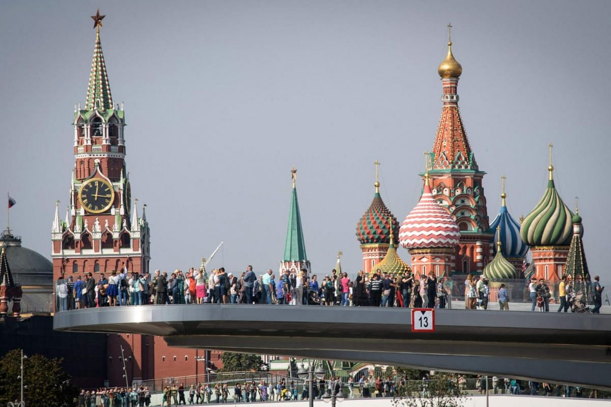People walk along a bridge in Zaryadye Park next to Saint Basil's cathedral (right) and Spasskaya tower (left) in central Moscow, on Sept 12, 2017.