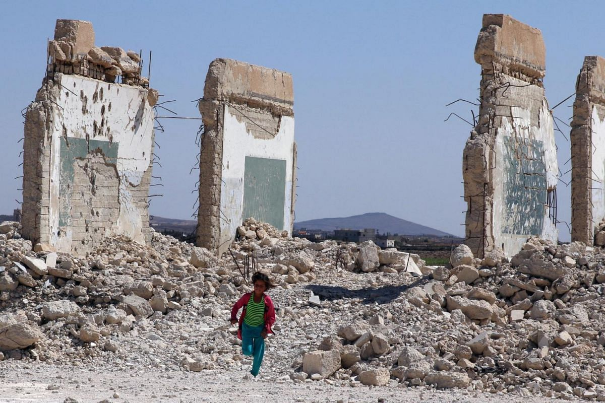 A girl runs near a damaged site in the Quneitra countryside, Syria, on Sept 12, 2017.