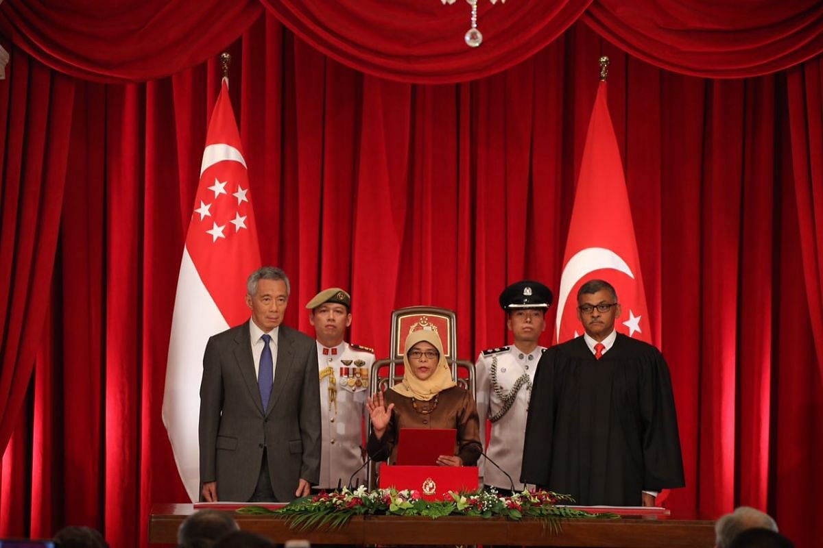 Madam Halimah Yacob taking her oath of office, while flanked by Prime Minister Lee Hsien Loong and Chief Justice Sundaresh Menon, at the Istana on Sept 14, 2017.