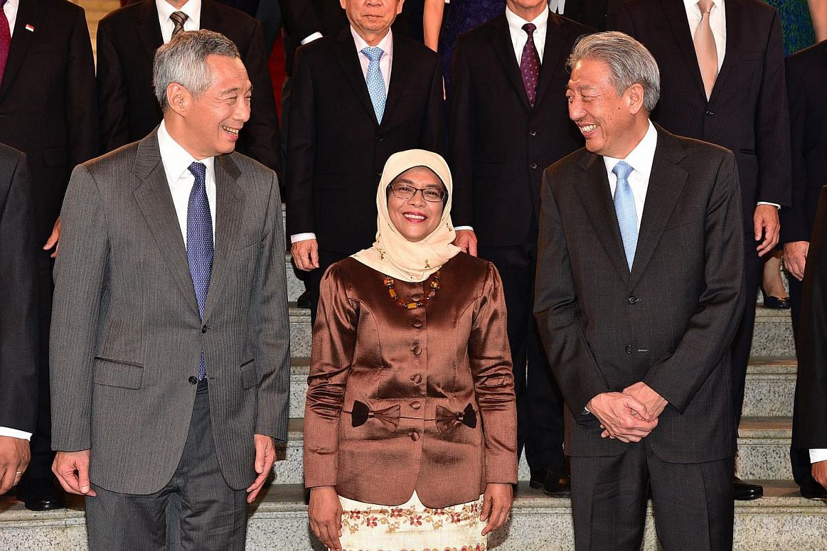 Madam Halimah Yacob standing between Prime Mininster Lee Hsien Loong and Deputy Prime Mininster Teo Chee Hean as they prepare to take a group picture at the Istana, on Sept 14, 2017.
