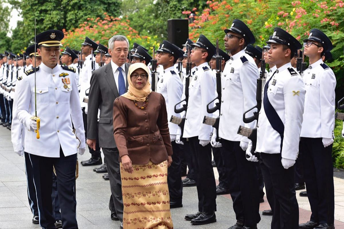 Madam Halimah Yacob inspecting the guard of honour, ahead of her swearing-in ceremony, at the Istana on Sept 14, 2017.