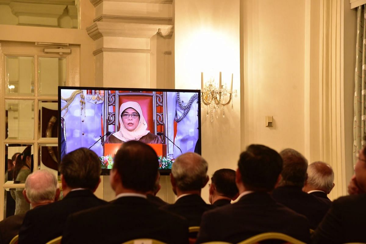 Guests watching President Halimah Yacob speaking live on a screen in the Istana's reception room, on Sept 14, 2017.