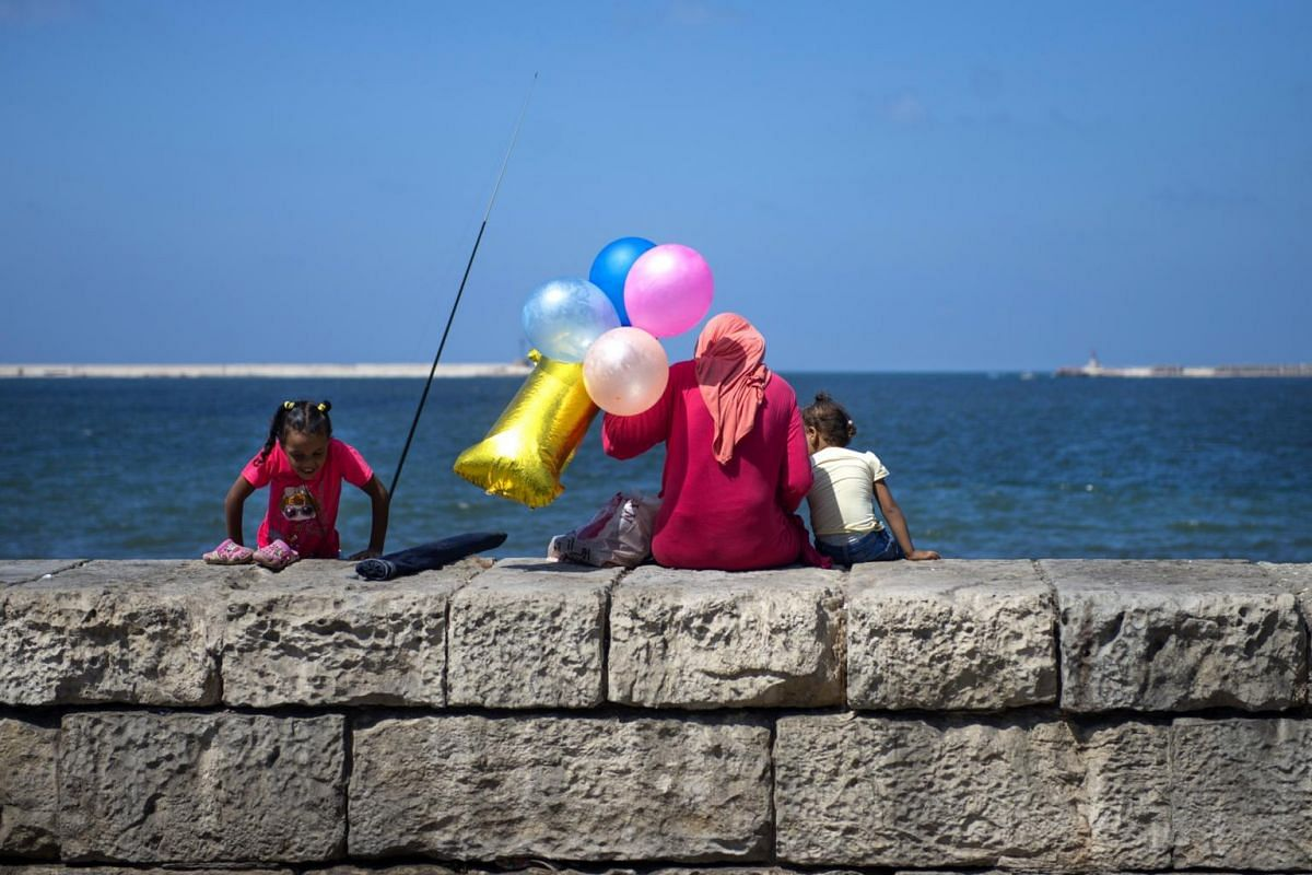 A family sits by the sea at the Corniche, in Alexandria, Egypt, on Sept 8, 2017.