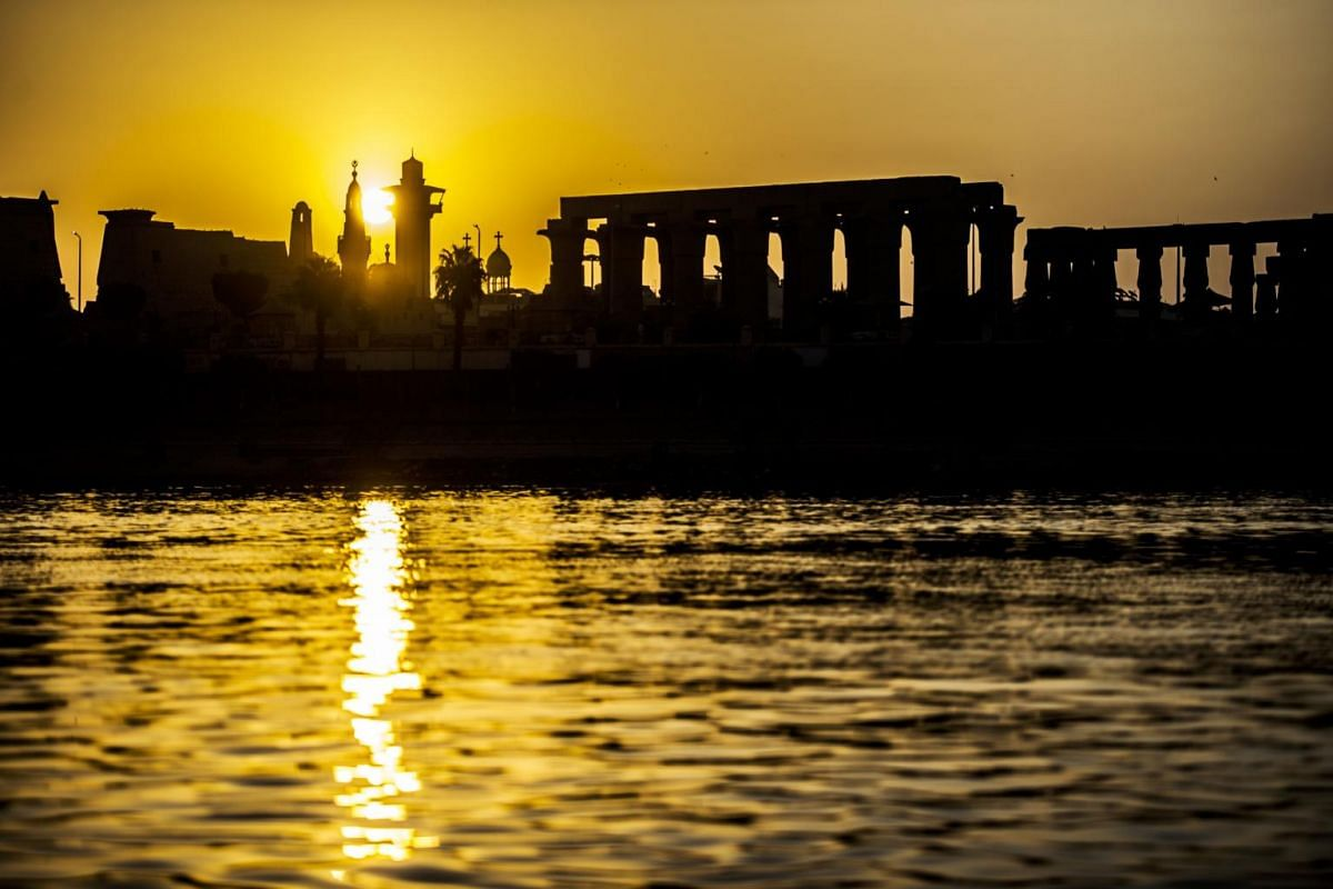 A  silhouette of the skyline of the southern Egyptian city of Luxor at sunrise, showing the pylons and columns of the ancient Egyptian Temple of Luxor and the minaret of the 13th century Abu Haggag mosque.