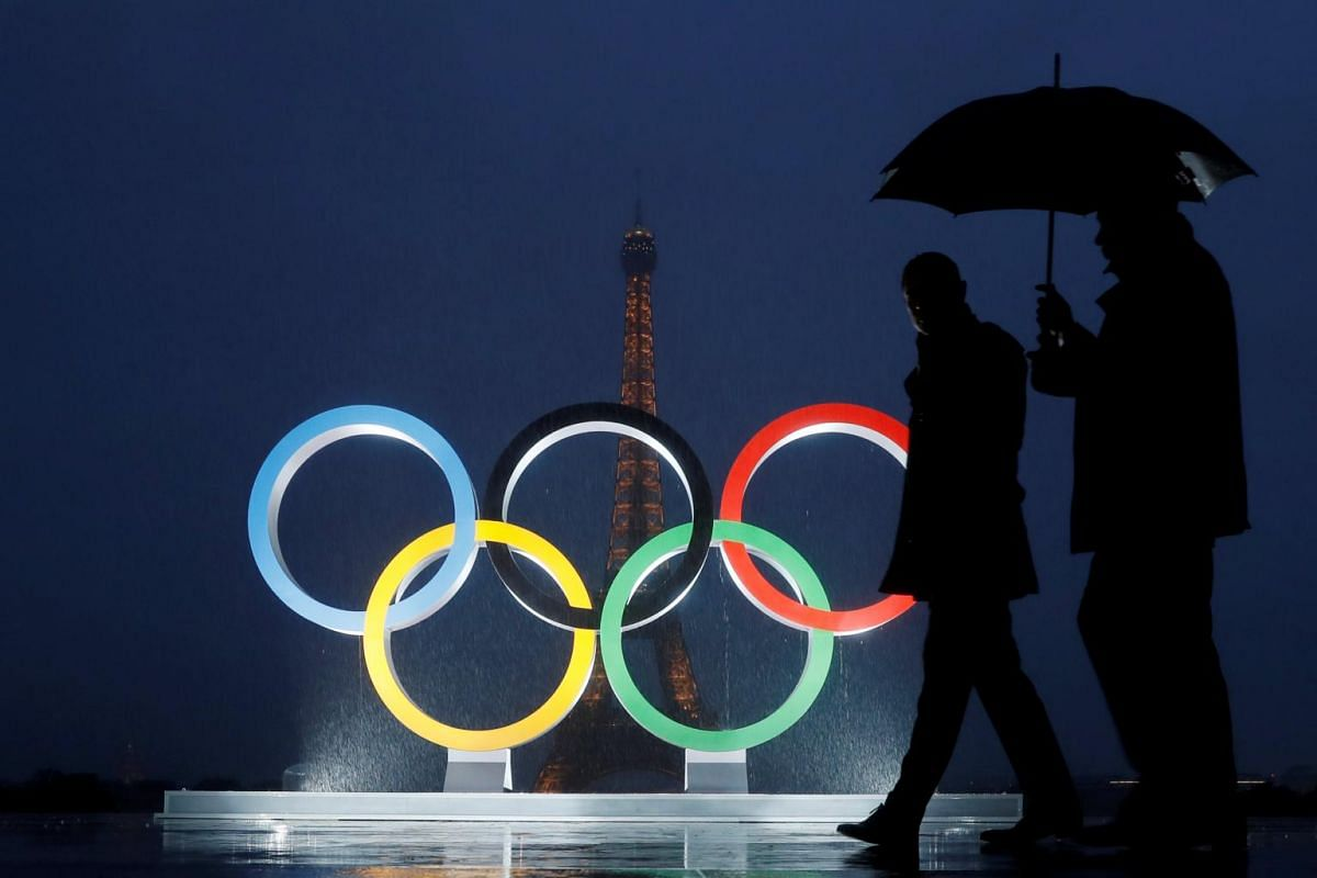 Men walk in the rain under an umbrella next to the Olympic rings after the IOC officially announced that Paris won the 2024 Olympic bid during a ceremony at the Trocadero square near the Eiffel Tower in Paris, France, on Sept 13, 2017.