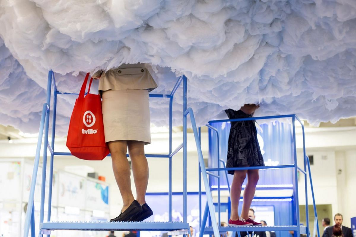 Attendees stand on step ladders to look inside a cloud display at an exhibition booth during the Mobile World Conference Americas event in San Francisco, California on Sept 12, 2017.