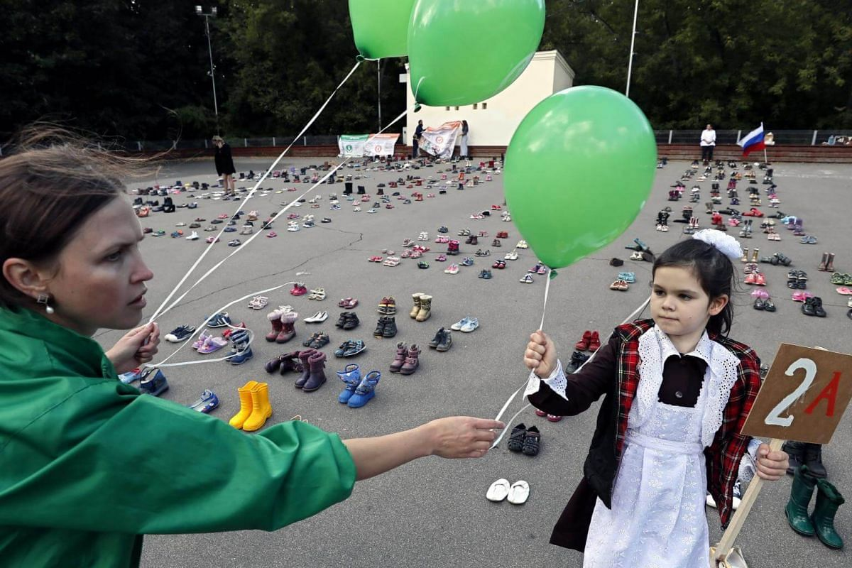 """A Russian woman and a little girl participate in a public action themed,""""In defense of human life from the moment of conception (They could go to school)"""", in Moscow, on Sept 14, 2017."""