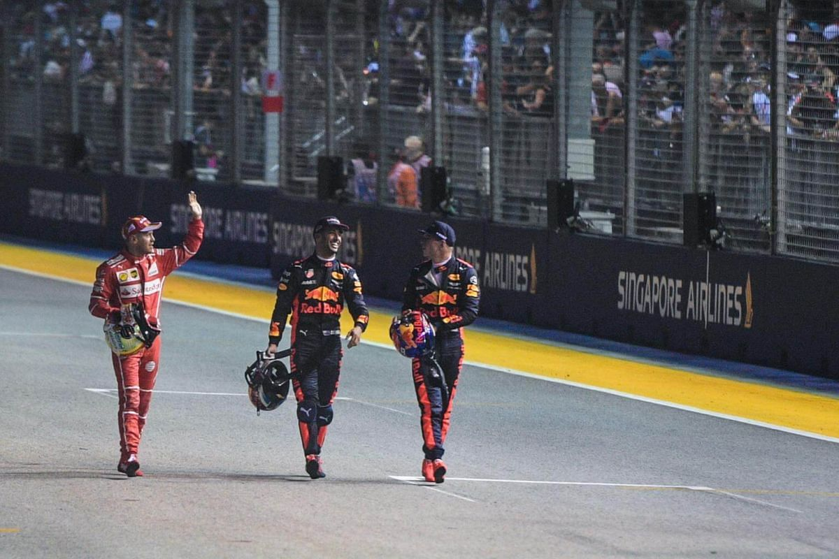 Top qualifier German driver Sebastian Vettel of Scuderia Ferrari waves next to the next to top qualifiers, Australian Daniel Ricciardo (centre) and Dutch Max Verstappen of Red Bull Racing Tag Heuer, on the track after the qualifying round on Sept 16,