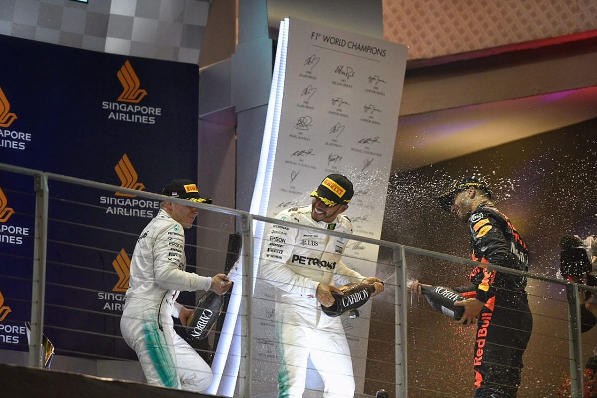 (From left) Red Bull's Daniel Ricciardo, Mercedes' Lewis Hamilton and his team-mate Valtteri Bottas spraying one another with champagne after the 2017 Formula One Singapore Grand Prix on Sunday, (Sept 17).