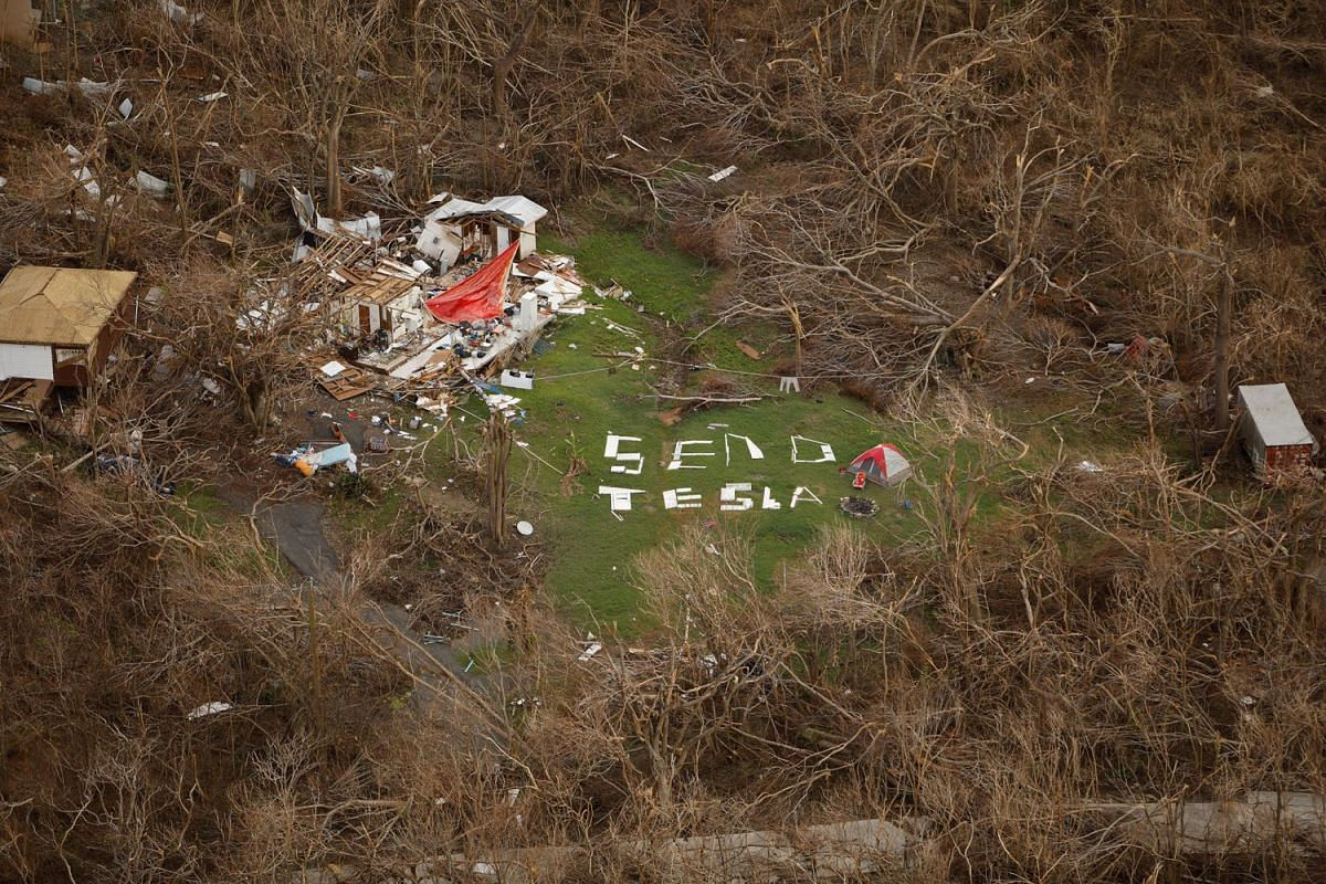 """A sign saying """"Send Tesla"""" is spelled out with remnants of a nearby house destroyed by Hurricane Irma as the occupant camps on the site twelve days after the devastating storm raked the island, on the northern shore of St. John, U.S. Virgin Islands S"""