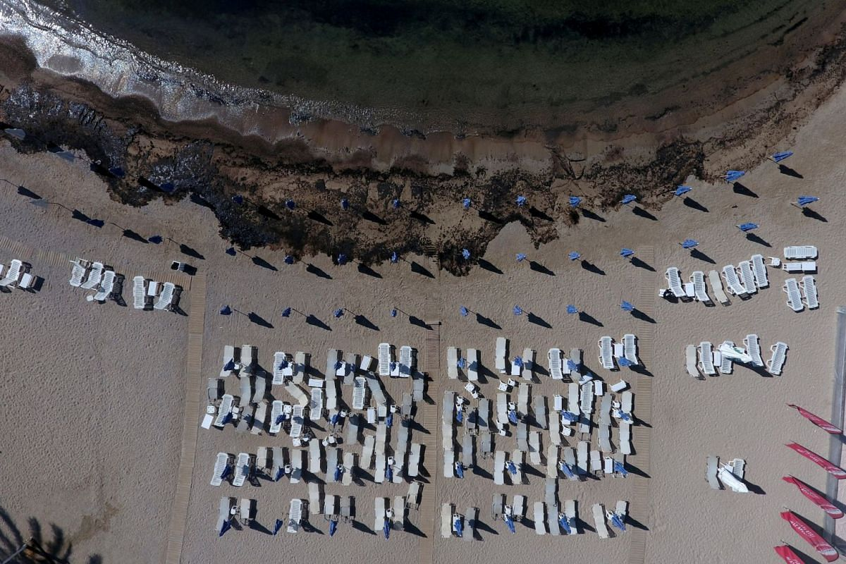 Oil that leaked from a small oil tanker that sank on September 10, is seen next to sunbeds and folded umbrellas on the beach of Agios Kosmas at the riviera in Athens, Greece, September 17, 2017. PHOTO: REUTERS