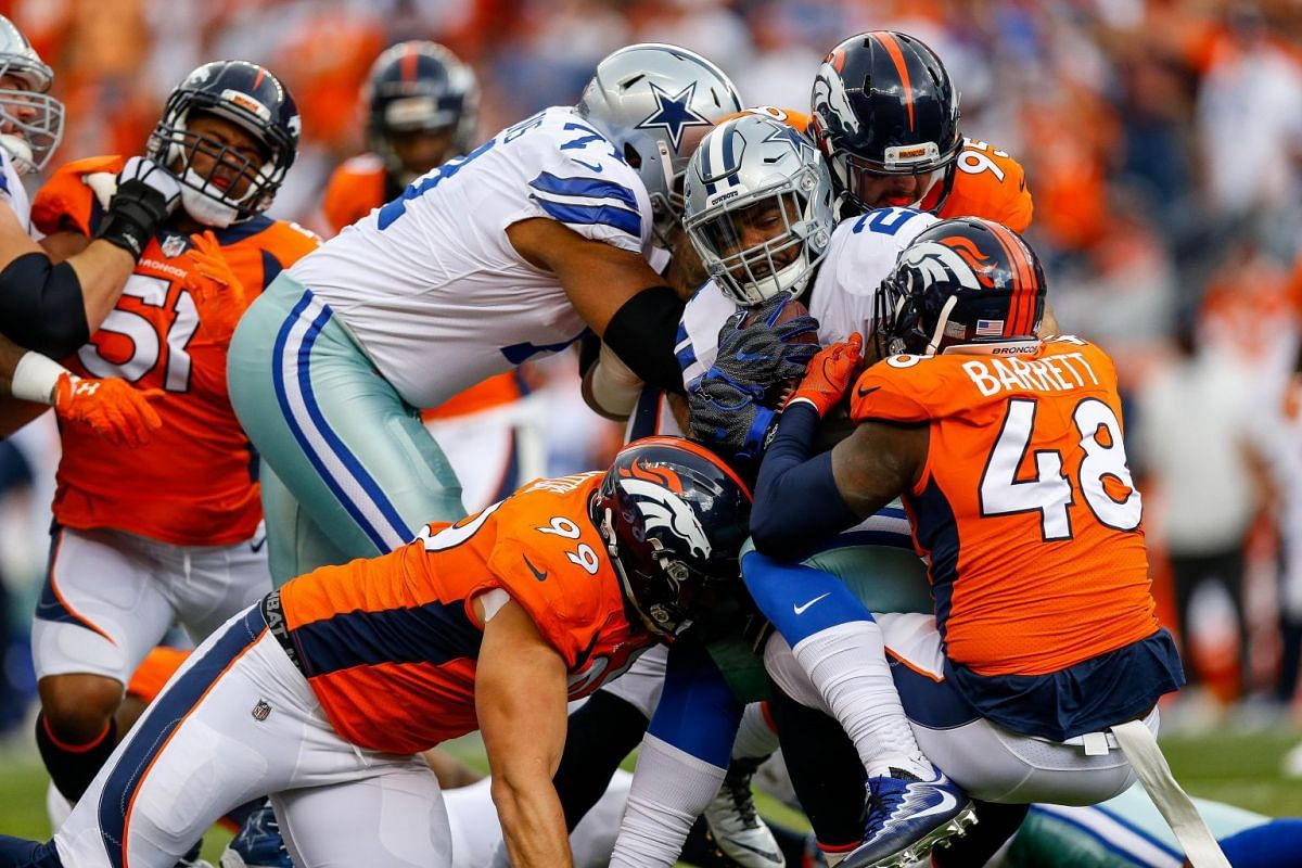 Running back Ezekiel Elliott #21 of the Dallas Cowboys is tackled by Adam Gotsis #99 and outside linebacker Shaquil Barrett #48 of the Denver Broncos in the first quarter of a game at Sports Authority Field at Mile High on September 17, 2017 in Denve