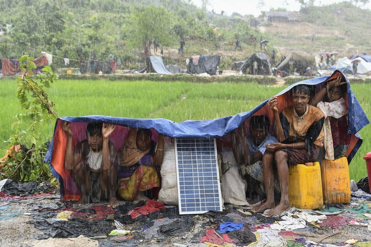 Rohingya refugees protect themself from the rain in Bangladesh's Balukhali refugee camp on September 17, 2017. PHOTO: AFP