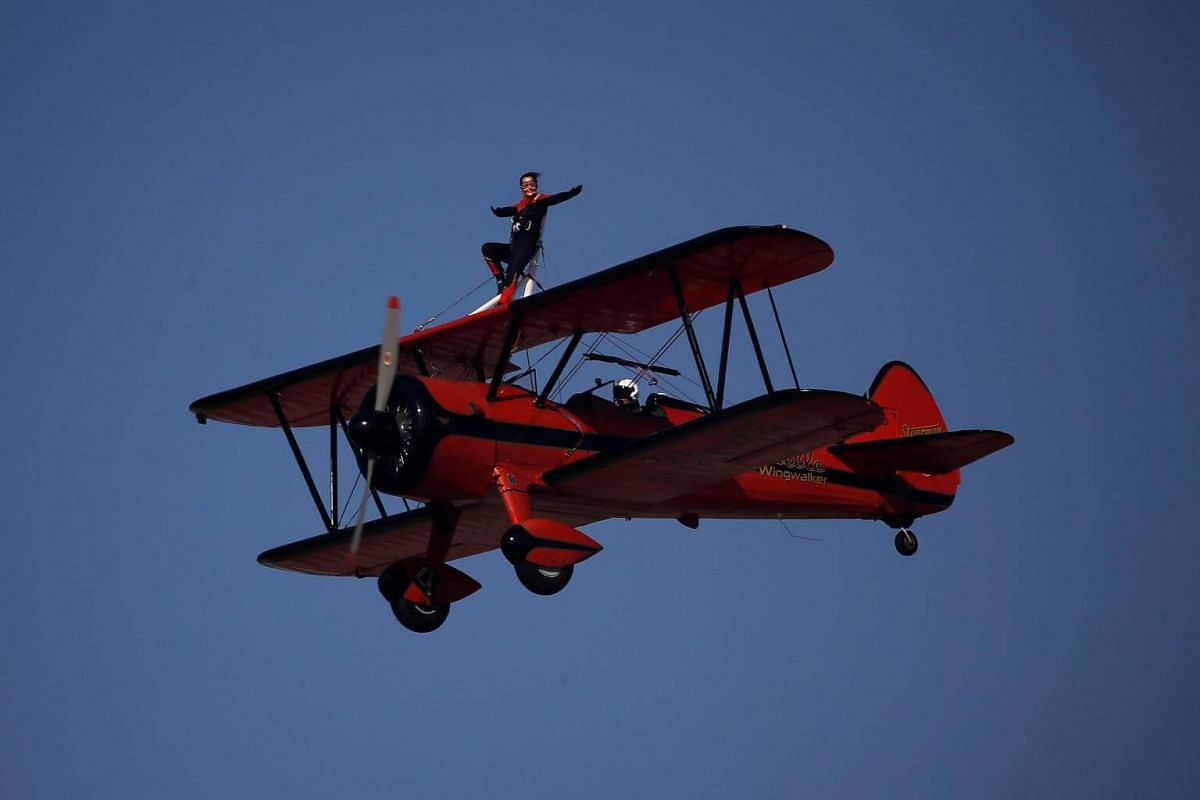 Danielle Hughes performs on a plane piloted by her husband Emiliano Del Buono during the 6th Athens Flying Week aviation event over the Tanagra air base in Athens, on Sept 17, 2017.
