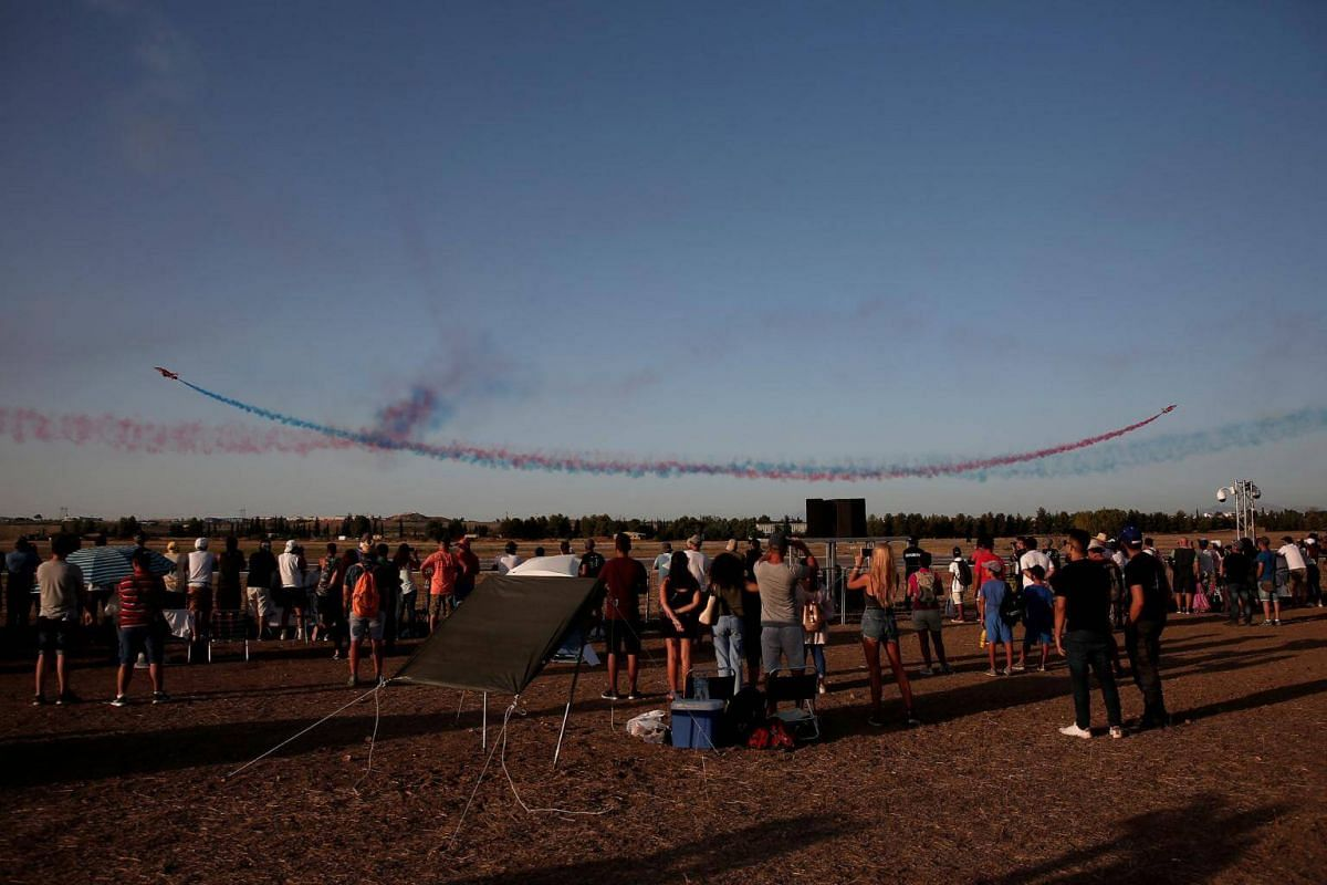 Spectators watch the Red Arrows RAF aerobatics display team performing during the 6th Athens Flying Week aviation event over the Tanagra air base in Athens, on Sept 17, 2017.