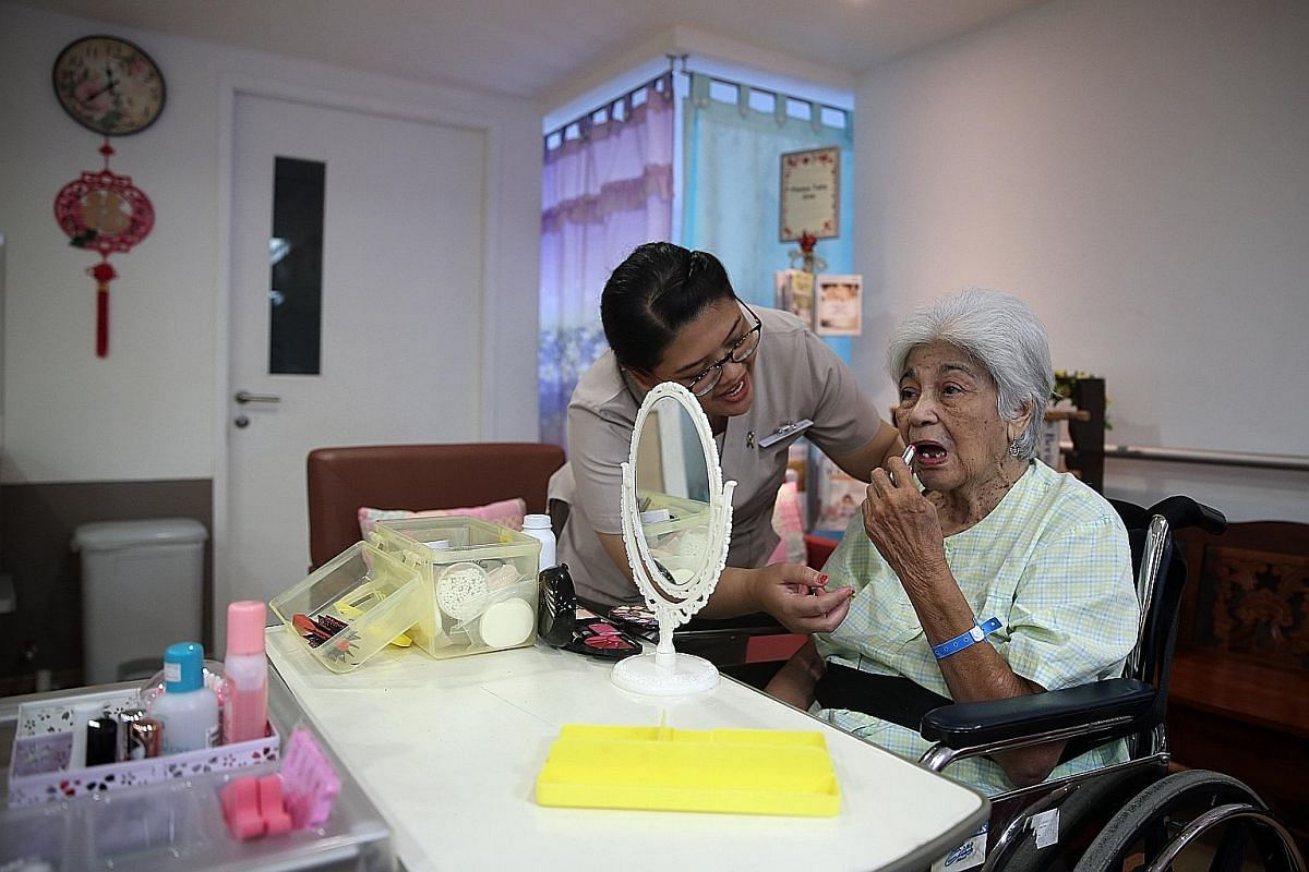 Senior nurse manager Lee Soh Luan wheels Madam Wong Soo Han, 87, near Madam Goh Chor Keng, 88, as they show off their dolls. Both patients have dementia and Madam Wong was admitted to hospital because of a fracture after a fall while Madam Goh had vi