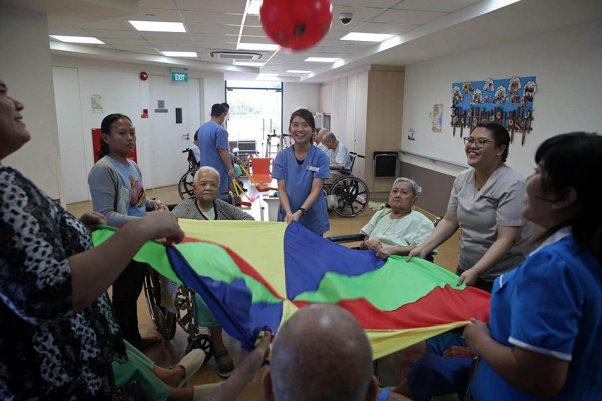 Physiotherapist Ms Rebecca Tan (centre, in blue) and therapy assistant Ms Syarifah Maisarah Syed Alwi (second from right) engage patients at the dementia care ward in a parachute activity as part of physiotherapy.