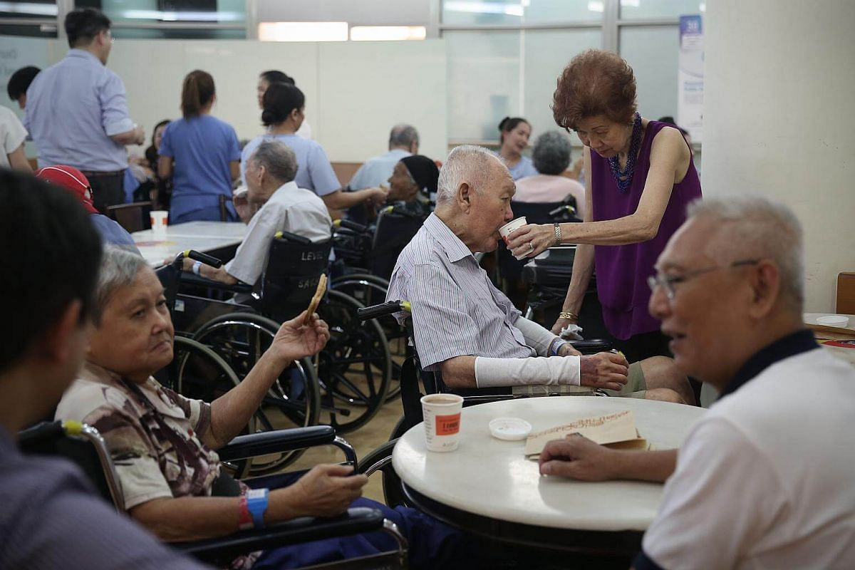 Mrs Rosalind Tan (in purple), 76, assists her husband Mr Tan Lye Kiat (centre), 84, to drink coffee as they take part in Memories Cafe, a collaborative programme with Alzheimer's Disease Association, that engages patients with dementia and their ca