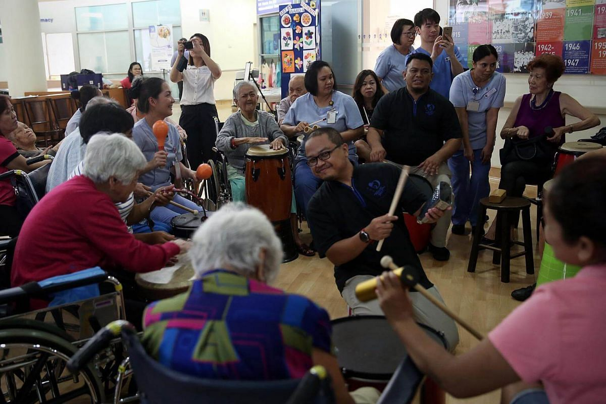Facilitator Aden Firdaus Jam'an (centre, in black) from OneHeartBeat Percussion engages patients from the dementia care ward in a rhythmn wellness programme using drums and other percussion instruments.