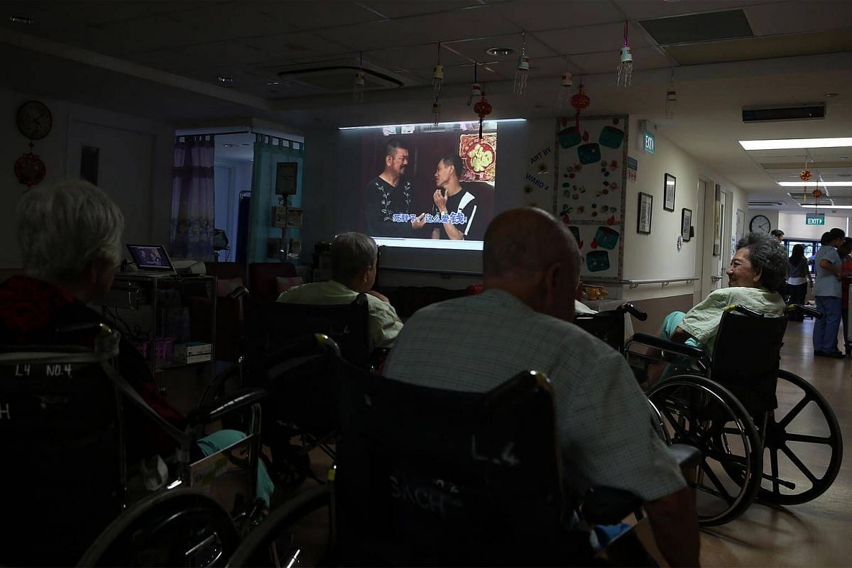 Madam Lim Kim Heang (extreme right), 76, watches a movie with other patients at the dementia care ward. Diagnosed with dementia, Madam Lim was admitted to SACH due to a kidney and urine infection. The founding philosophy of this 22-bed dementia ward