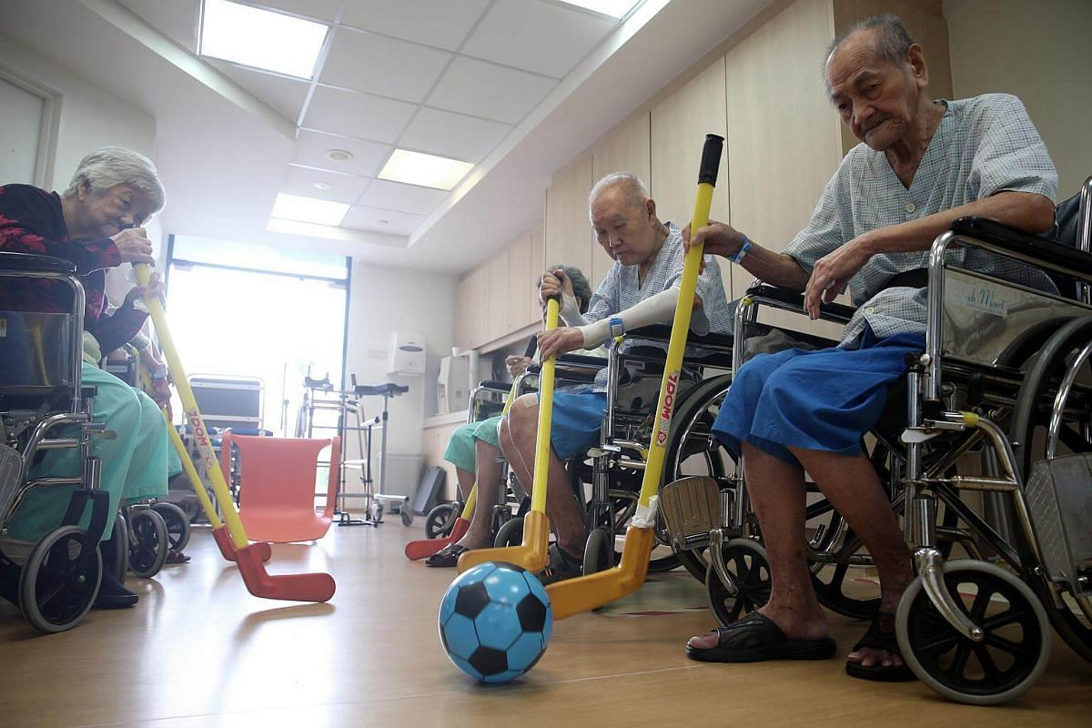 84-year-old Mr Tan Lye Kiat (second from right), plays an improvised game of hockey with Mdm Goh Ah Hiang (extreme left), 91, and Mr Lee Kong Foo (extreme right), 88, at the dementia care ward. Mr Tan was admitted to SACH because he suffered a stroke